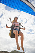 Smiling female paraglider mid-air