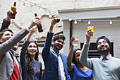 Friends toasting drinks at party on patio
