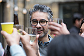 Happy man toasting drinks with friends at party