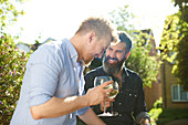 Happy male gay couple drinking wine