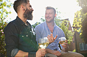 Smiling male gay couple drinking white wine