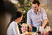 Happy family enjoying candlelight Christmas dinner