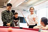 Happy teenagers playing pool