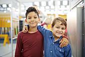 Portrait cute boys hugging in science centre