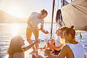 Friends drinking champagne on sunny catamaran