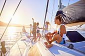 Playful friends playing guitar on sunny catamaran