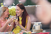 Lesbian couple drinking white wine on patio