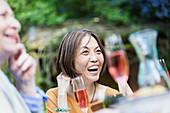 Laughing senior woman enjoying garden party