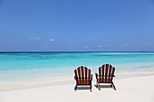 Two adirondack chairs on beach