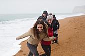 Happy, carefree family on snowy winter beach
