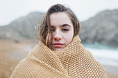 Girl with snow in hair wrapped in blanket