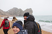 Portrait father and son walking on snowy beach