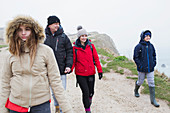 Family walking on snowy winter cliff path