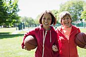 Senior women friends playing basketball