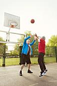 Active senior men friends playing basketball