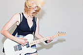 Exuberant young woman playing electric guitar