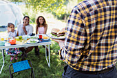 Father serving barbecue hamburgers to family table