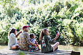 Family blowing bubbles on dock in woods
