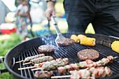 Man barbecuing hamburgers, kebabs and corn cobs