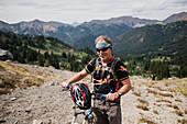 Portrait senior man mountain biking in landscape, Canada