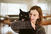 Portrait girl holding hissing black cat