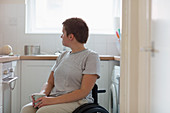 Thoughtful woman in wheelchair drinking tea