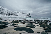 Rocks on snowy, beach, Lofoten Islands, Norway