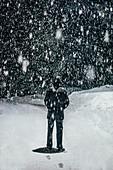 Snow falling over man