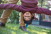 Playful boy hanging upside down