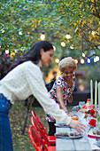 Women friends setting table for dinner garden party
