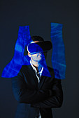 Businessman with VR simulator glasses and AI text