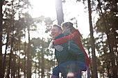 Happy, playful couple piggybacking in sunny woods