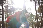 Couple piggybacking in sunny, autumn woods