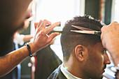 Male barber giving customer a haircut in barbershop