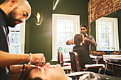 Male barbers working in barbershop