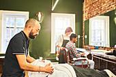 Male barber steaming face of customer in barbershop