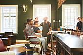 Male barbers and customers in barbershop