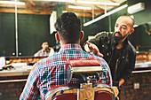 Male barber checking haircut of customer in barbershop