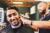 Portrait smiling young man receiving haircut