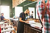 Male barber looking at schedule in barbershop