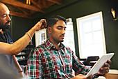 Man using digital tablet while receiving haircut