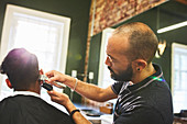 Male barber with trimmers giving customer haircut