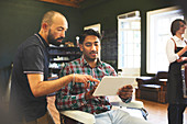Male barber and customer with digital tablet talking