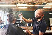 Male barber spraying hair of customer in barbershop