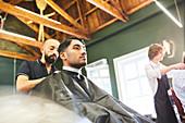 Male customer getting a haircut in barbershop