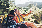 Happy mother and daughters taking selfie, hiking