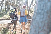 Young women friends with backpacks hiking