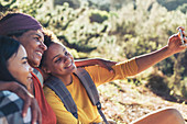 Happy mother and daughter hikers taking selfie