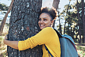 Happy, carefree young female hiker hugging tree
