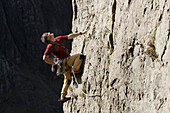 Male rock climber scaling rock face, looking up